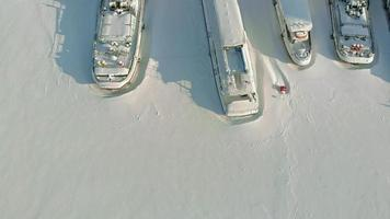 Large river ships in the winter parking lot The ships are frozen in the ice Aerial filming video