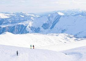 Panoramic view of Caucasus mountains with three skiers on the hill posing photo