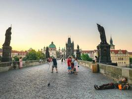 Prague, 2018- Sleeping homeless with tourists around on Charles bridge in Prague early in the morning photo