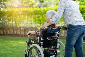 Doctor help and care Asian senior or elderly old lady woman patient sitting on wheelchair at park in nursing hospital ward healthy strong medical concept photo