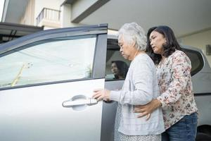 Help and support asian senior or elderly old lady woman patient sitting on wheelchair prepare get to her car healthy strong medical concept photo