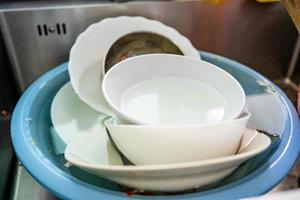 Used dishes prepared to wash on the kitchen sink photo