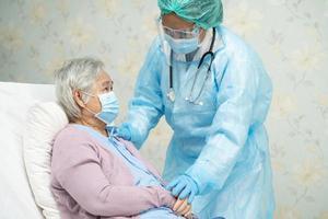 médico asiático con protector facial y traje de ppe nuevo normal para comprobar el paciente protege la seguridad infección brote de coronavirus covid 19 en la sala de cuarentena del hospital de enfermería foto