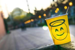 Yellow disposable paper cup and smiley face on it standing on the side of shelf with blue mosque in the background photo