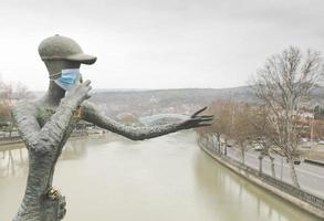 Tbilisi, Georgia 2020- Statue named Photographer with face mask on Nikoloz Baratashvili Bridge photo