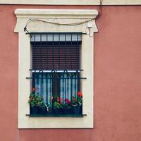 ventana en la fachada rosa de la casa foto