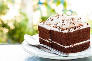chocolate cakes with white cream on top and spoon on plate and bokeh at background photo