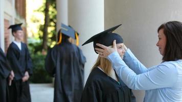 mère prépare sa fille pour la cérémonie de remise des diplômes video