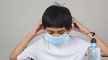 Closeup of a boy face wearing a sanitary napkin mask and washing his hands with alcohol gel video