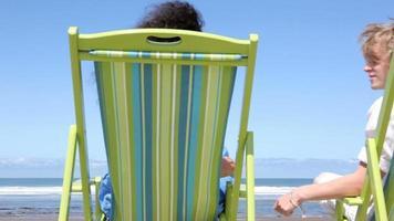 par sitter i stolar på stranden kyss video