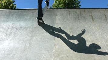 Ombre du skateboarder coulissant quart de tuyau en béton video