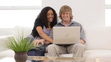 couple assis sur un canapé avec un ordinateur portable video