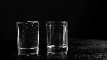 Vodka is poured into two glasses on black background video