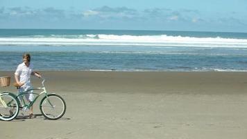 paar lopen met fietsen langs de kustlijn video