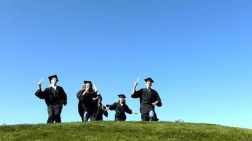 diplômés qui courent sur la colline, au ralenti video