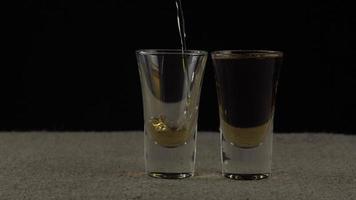 le whisky est versé dans deux verres sur fond sombre video