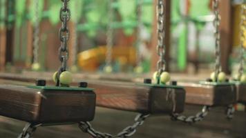 Pont suspendu en bois sur les chaînes se balançant sur l'aire de jeux video