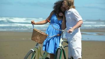 coppia con biciclette in spiaggia video