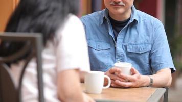 casal asiático maduro tomando café em um café ao ar livre video
