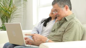 casal asiático maduro usando laptop video