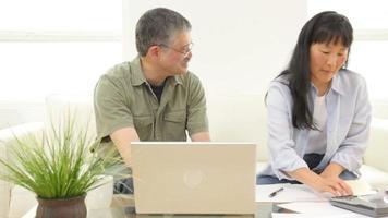 casal asiático maduro trabalhando nas finanças pessoais video