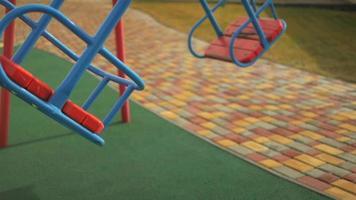 deux balançoires vides se balancent sur l'aire de jeux pour enfants video