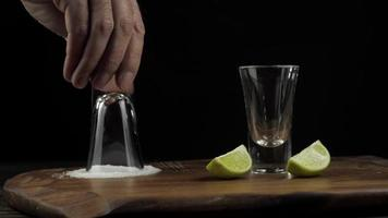 Bartender prepares tequila and dabs a stick in the salt next to the lime video
