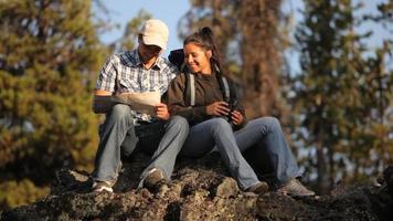 pareja sentada sobre una roca mirando el mapa video