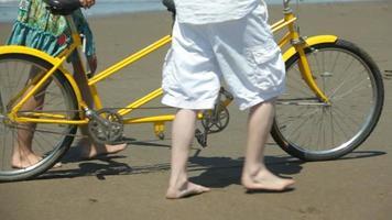 paar wandelen op strand met tandem fiets video