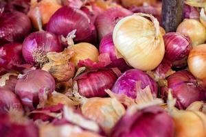 Montón de cebollas rojas y blancas en el mercado verde foto