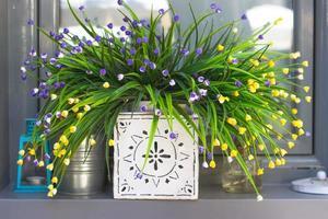 flores artificiales decorativas en el alféizar de la ventana foto