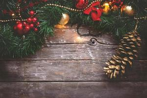 Christmas background  garland golden and red ornaments and pine cone on dark wooden background photo