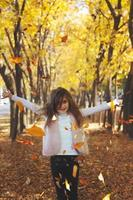 Beautiful little girl throwing fallen leaves playing in the park autumn nature background photo