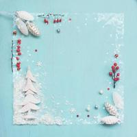 White pine cone ornaments and red berries on blue background Christmas background with copy space photo
