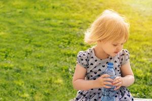 niña pequeña sosteniendo una botella de agua foto