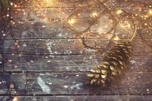 Christmas background  christmas lights and pine cone on dark wooden background with golden glitter photo
