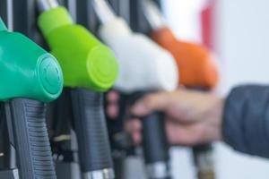boquillas de la bomba de combustible para diferentes tipos de combustible en una estación de servicio foto