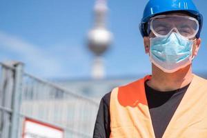 Trabajador de la construcción vistiendo casco azul, chaleco reflectante y mascarilla quirúrgica protectora foto