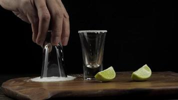 The bartender prepares tequila and dabs a stick in the salt video