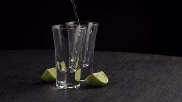 Tequila is poured two glasses on black background video