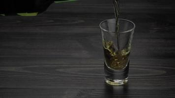 Tequila is poured into a glass with ice video