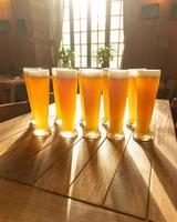 A lot of beer mugs on the table with sun shine through the glass window photo
