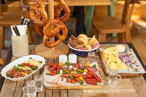 salchichas con queso y pepinos fermentados, bocadillos de pretzel con vodka en la mesa foto