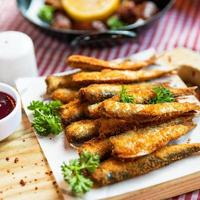 Kilka, Sprat fish, ketchup, and other snacks on the table photo