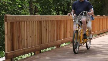 casal asiático maduro andando de bicicleta tandem pela ponte video