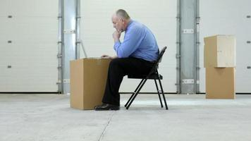 Business man in warehouse with laptop on cardboard box video