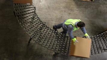 homem no armazém de transporte move caixas ao longo da esteira video