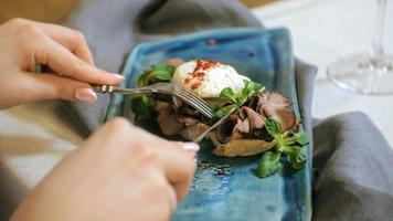 Close up shooting a delicious bruschetta with beef poached egg and lettuce leaves video