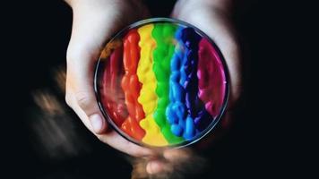 Peinture en remuant arc-en-ciel multicolore tenant sur la main de la paume avec la fumée 3d concept festival holi couleur arc-en-ciel magique video