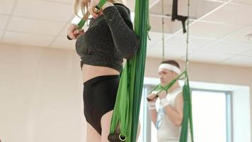 Yoga antiaérien aérien dans la salle de sport groupe de personnes se balançant dans les hamacs video